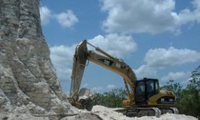 A digger claws away on sloping edges of the Mayan pyramid in Belize