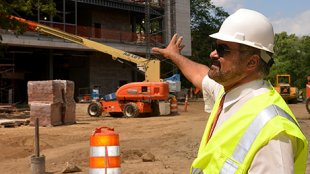 Amr Abdel-Azim gestures toward the newly-constructed Wells Hall.